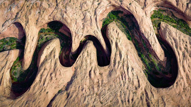 La vegetación verde florece en el borde del río de un cañón serpenteante en Utah.