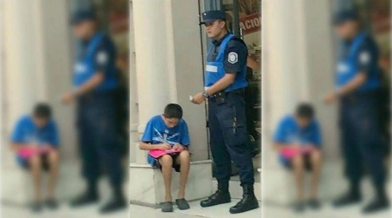 La conmovedora foto de un policía de 20 años que ayuda a estudiar a un nene en la calle