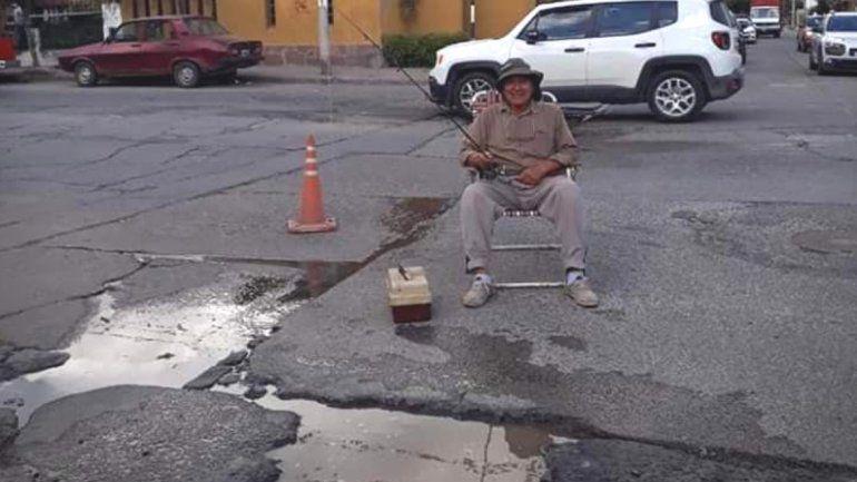 Se puso a pescar en plena calle para reclamar por un enorme bache
