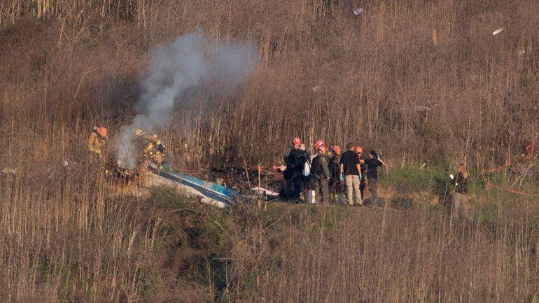 Bomberos junto a los restos del helicóptero donde murió el astro de la NBA.